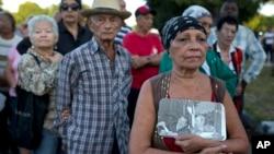 28일 쿠바 수도 아바나 시내 혁명광장에 피델 카스트로 전 국가평의회 의장 추모객들이 모여들고 있다. 맨 앞의 여성은 지난 2013년 사망한 우고 차베스 전 베네수엘라 대통령과 카스트로 전 의장이 함께한 사진을 들고 있다.