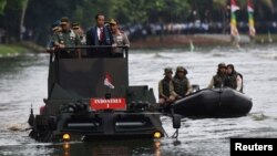 (L-R) Indonesia Military Chief Gatot Nurmantyo, Indonesia President Joko Widodo, and Indonesia Police Chief Tito Karnavian stand on a military amphibious vehicle Anoa 2 while crossing a lake at a military headquarters in Jakarta, Jan. 16, 2017.