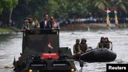Presiden Joko Widodo, bersama Panglima TNI Jenderal Gatot Nurmantyo (kiri) dan Kapolri Jenderal Tito Karnavian (kanan), menyeberangi danau di Jakarta dengan memakai kendaraan amfibi militer Anoa 2 (16/1).