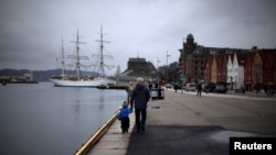 FILE - A man walks with a child near the marina in downtown Bergen, southwestern Norway, March 20, 2012.