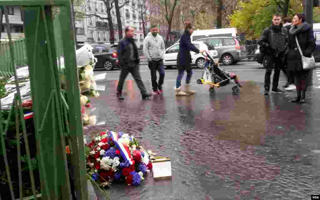 People walk past a plaque near Cafe Bonne Biere where jihadists shot dead 5 people last year, in Paris, Nov. 13, 2016. (L. Bryant/VOA)