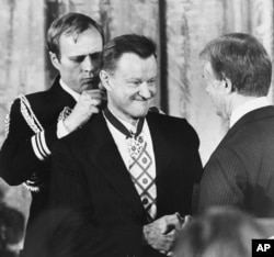 President Carter shakes hands with his national security adviser, Zbigniew Brzezinski, as he presents Brzezinski with the Medal of Freedom at a White House ceremony, Jan. 17, 1981 in Washington.