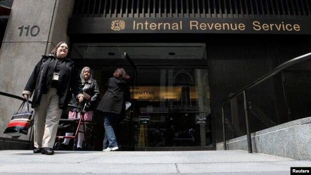 FILE - Women walk out of an Internal Revenue Service office in New York.