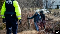FILE - Two people who later indicated to officials they are from Sudan cross into Canada from Perry Mills, N.Y., near Hemmingford, Quebec, Feb. 26, 2017.