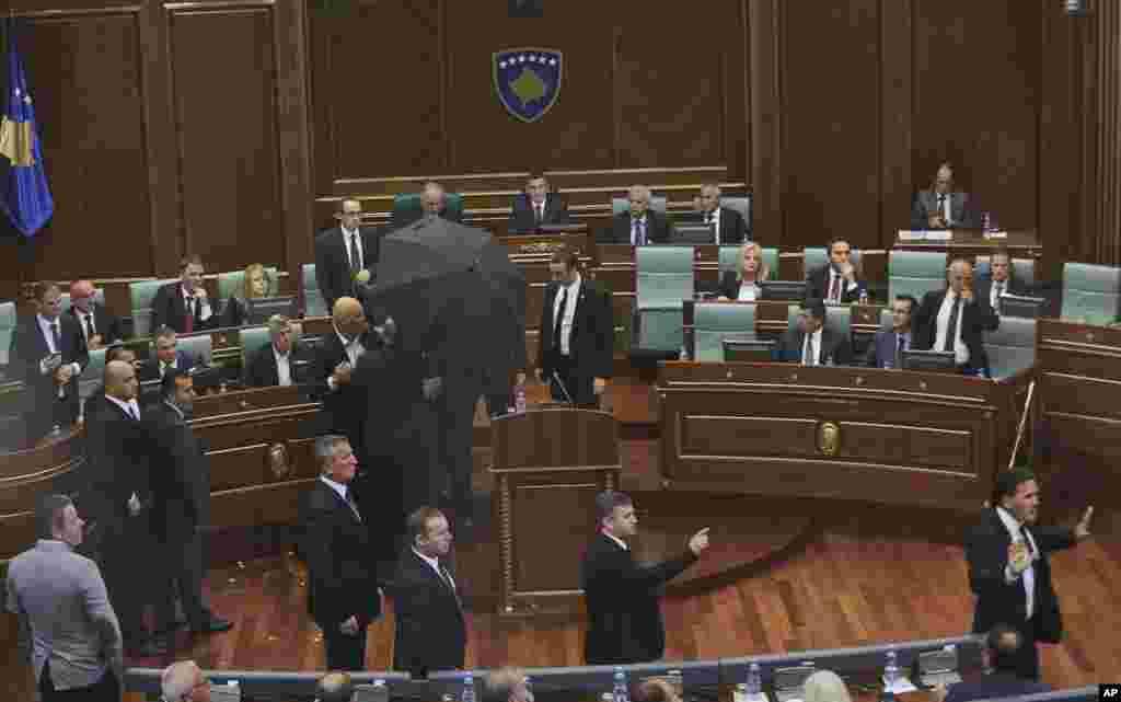 Bodyguards escort Kosovo's Prime Minister Isa Mustafa, covering with an umbrella, away from the stand as opposition members hurl eggs while he is addressing parliament in capital Pristina, on the latest agreement reached between Kosovo and Serbia.