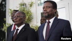 Haiti's provisional president Jocelerme Privert (L) and appointed prime minister Fritz Jean listen to the national anthem at Jean's inauguration ceremony in the National Palace in Port-au-Prince, Haiti, Feb. 26, 2016.