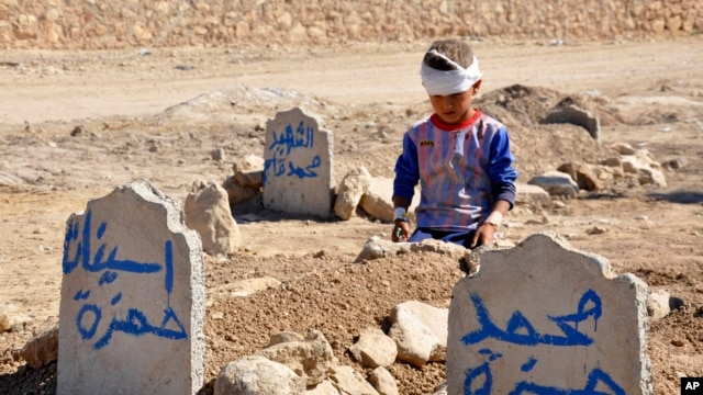 Ali Hamza, 8, at the graves of his brother, Mohammed, and sister, Asinat, who were killed at school by a nearby suicide car bombing, Qabak, Iraq, Oct. 7, 2013.