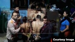 Men arrested at the Bab el-Bahr public bath house are herded into a police van, Dec. 7, 2014. Egyptian journalist Mona Iraqi appears at right, with camera phone. Screenshot from Mona Iraq's Facebook page, courtesy Scott Long