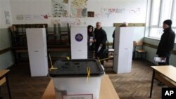 A Kosovo couple prepare to vote at a polling station in general elections in Kosovo's capital Pristina, 12 Dec 2010
