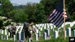 Miembros del Tercer Regimiento de Infantería, The Old Guard, colocan banderas estadounidense en el Cementerio Nacional de Arlington, previo al Memorial Day o Día de los Caídos.