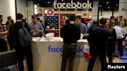 FILE - People stop at the Facebook booth at the Conservative Political Action Conference (CPAC) at National Harbor, Maryland, U.S., Feb. 23, 2018.