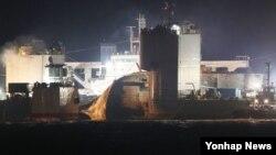 사고해역을 떠난 세월호가 24일 뭍으로 안전하게 옮겨줄 반잠수식 선박에 도착해 선적작업이 진행되고 있다.