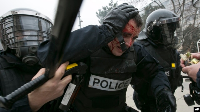 An injured policeman is helped by colleagues during a protest in Kosovo's capital Pristina, Jan. 27, 2015