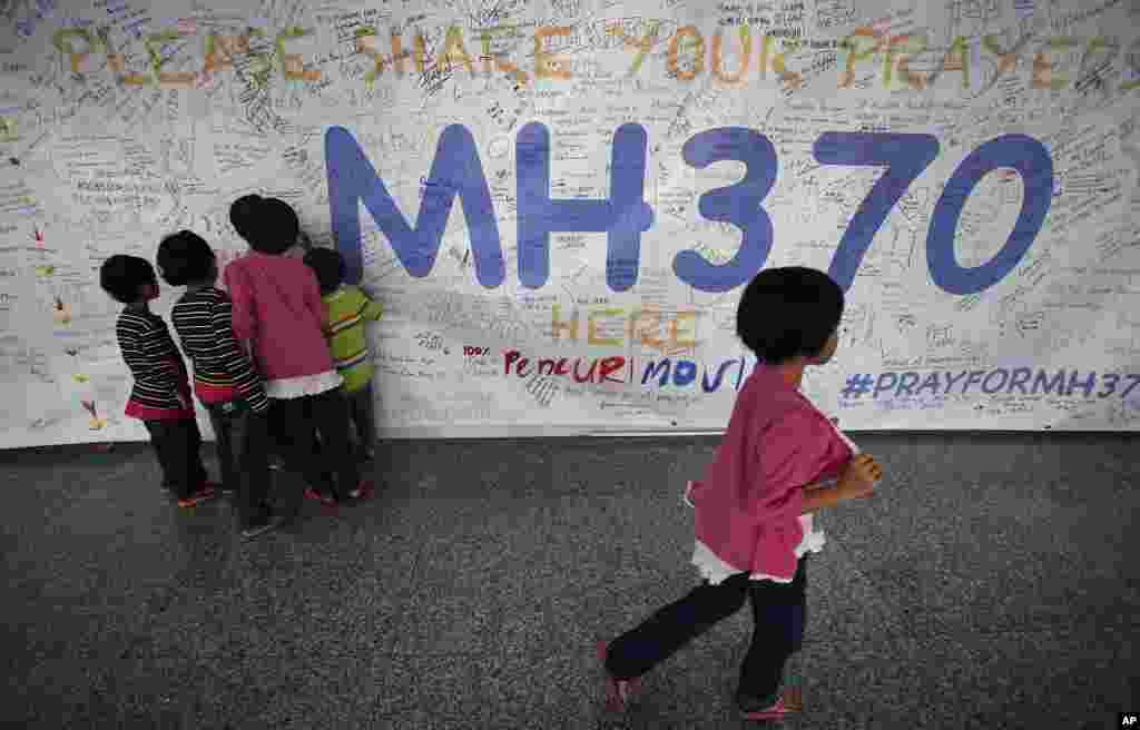 Children read messages and well wishes for all involved with the missing Malaysia Airlines jetliner MH370 on the walls of the Kuala Lumpur International Airport, March 13, 2014.