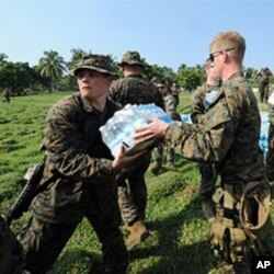 U.S. Marines load a U.N. truck with water to be distributed among Haitian earthquake survivors in Leogane, 20 Jan 2010