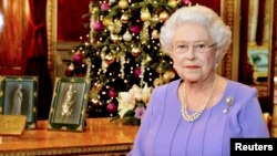 FILE - Britain's Queen Elizabeth poses for a photograph as she stands in the State Dining Room of Buckingham Palace, after recording her Christmas Day television broadcast to the Commonwealth, in London, Dec. 10, 2014.