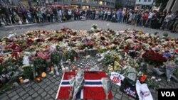 Para warga Norwegia mengenang korban tewas akibat serangan bom dan penembakan dengan meletakkan karangan bunga di ibukota Oslo (23/7).