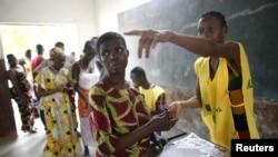 Un membre d'un bureau de vote de Cotonou, au Bénin, montre du doigt un isoloir, le 6 mars 2016. (REUTERS/Akintunde Akinleye)