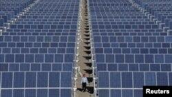 一名员工走行在敦煌郊外太阳能发电厂太阳能电池板之间
