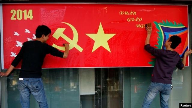 Công nhân đánh bóng poster mừng Tết Nguyên đán trên đường phố ở Hà Nội, ngày 23/1/2014.