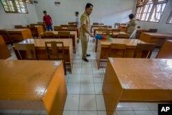 Anggota staf sekolah membersihkan ruang kelas setelah sekolah ditutup untuk mencegah penyebaran virus corona di Solo, Jawa Tengah, 16 Maret 2020. (Foto: AP)
