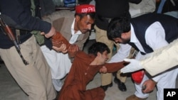 People try to comfort a boy who lost his family member, at a local hospital in Peshawar, Pakistan, Monday, Feb 27, 2012.