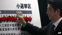 Ông Shinzo Abe, nhà lãnh đạo đảng Dân chủ Tự do, đang đối lập chính của Nhật Bản, đánh dấu tên của người đắc cử trong cuộc bầu cử quốc hội 16/12/12
