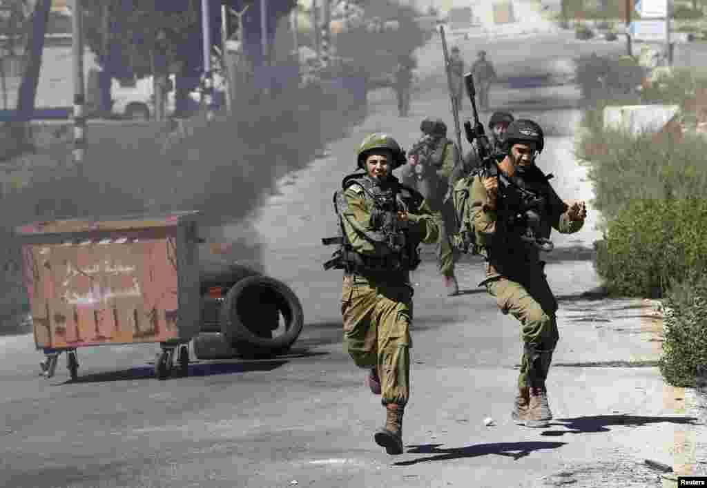 Israeli soldiers run during clashes with Palestinian protesters at a demonstration against the Israeli offensive in Gaza, near the Israeli settlement of Bet El, near Ramallah, July 25, 2014.