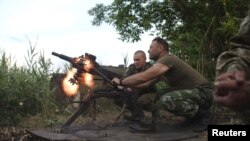FILE - Members of the Ukrainian armed forces fire a grenade launcher, in response to what servicemen said were shots fired from the positions of fighters of the separatist self-proclaimed Donetsk People's Republic, in the town of Avdiivka, Donetsk region,