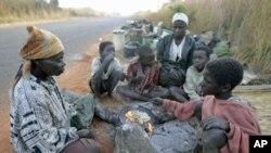 Familiares de trabalhadores expulsos tomam o pequeno almoço à berma de uma estrada.