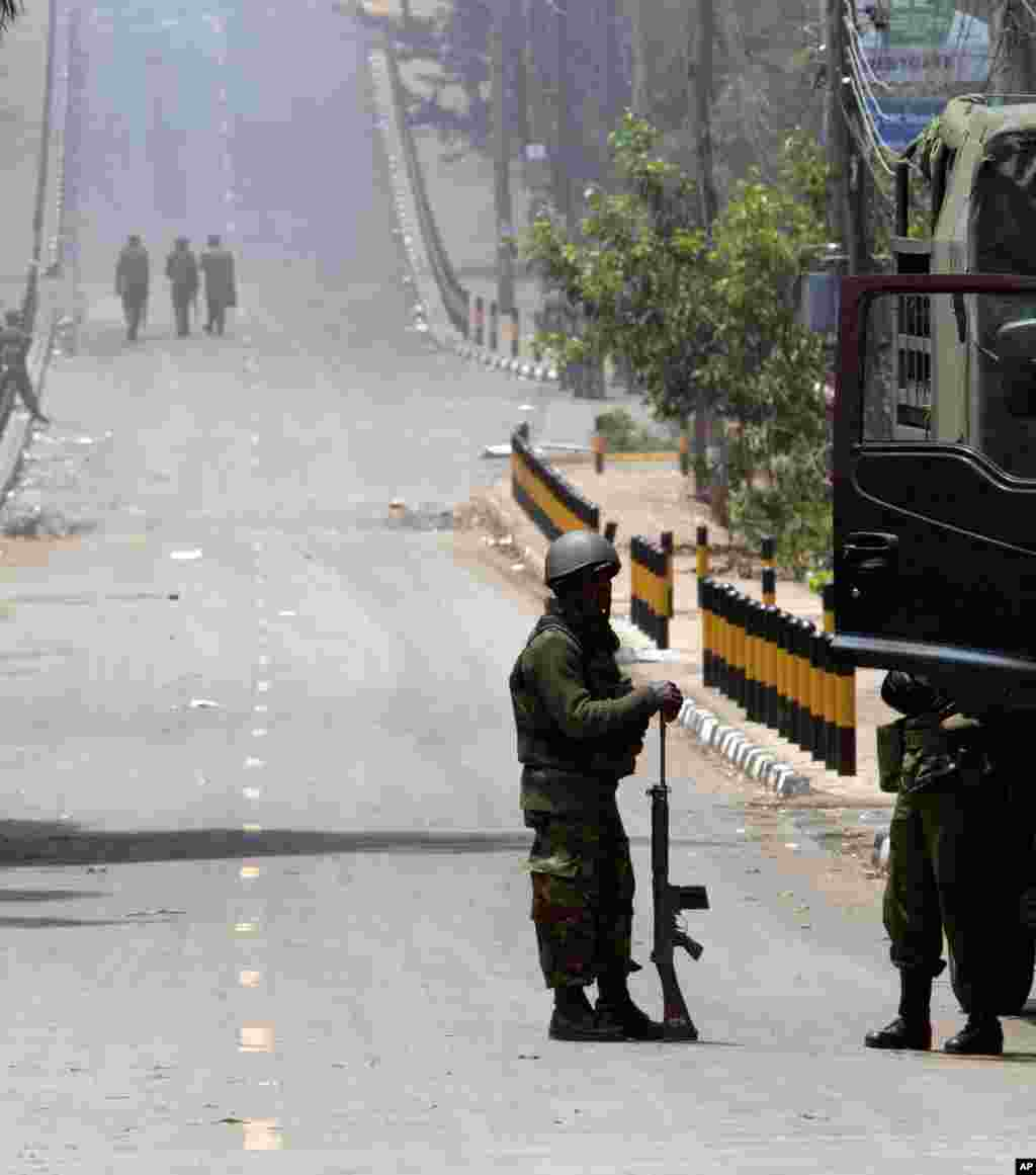 A Kenya Defense Forces soldier stands resting with his gun while others patrol on the empty road near the Westgate Mall in Nairobi, Sept. 25, 2013.