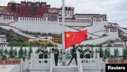 资料照:中国士兵在西藏拉萨布达拉宫前升起国旗。(2017年7月1日)