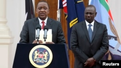 FILE - Kenyan President Uhuru Kenyatta, left, with Deputy President William Ruto, addresses a news conference at the State House in Nairobi, Dec. 2, 2014.