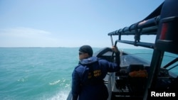 A Malaysia Maritime officer looks out into the sea during a search and rescue in Kuala Langat outside Kuala Lumpur, off Malaysia's western coast, June 18, 2014.