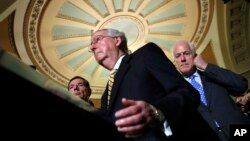 Senate Majority Leader Mitch McConnell of Kentucky, center, with Senate Majority Whip John Cornyn of Texas, right, and Sen. John Barrasso of Wyoming, talks to reporters on Capitol Hill in Washington, July 25, 2017.