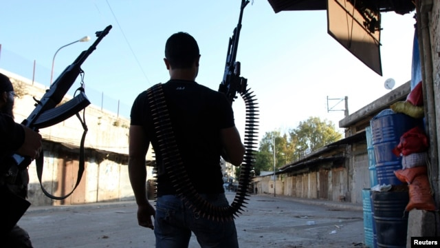 Two Lebanese Sunni gunmen hold weapons in Bab Al Tabbaneh, a Sunni district, in the northern Lebanese town of Tripoli May 26, 2013.