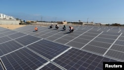 Palestinian workers install solar panels