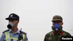 Seorang hansip dan polisi China, keduanya mengenakan masker berjaga di dekat lokasi ledakan di distrik Binhai, Tianjin, China hari Selasa (18/8).