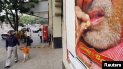 FILE - A man and child walk past a billboard showing Bollywood star Bachchan smoking in one of his films, in Bombay, India.