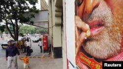 Seorang pria dan anak berjalan di depan poster iklan menunjukkan bintang Bollywood Bachchan merokok di salah satu filmnya, di Bombay, India.