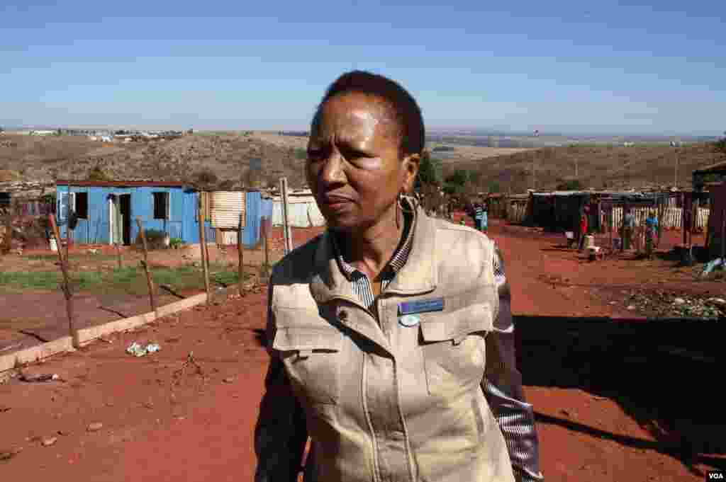 Nkoana trudges up a street in Munsieville, an impoverished township near Krugersdorp. She says after years of public health campaigns too many South Africans still die as a result of HIV. (Photo by Darren Taylor)