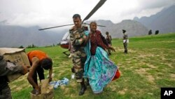 Indian army soldier helps an injured Indian pilgrim after she was rescued from the higher reaches of mountains, at a makeshift helipad at Joshimath, in northern Indian state of Uttarakhand, June 24, 2013.