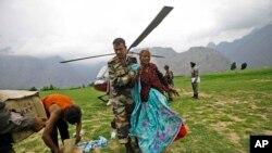 ທະຫານກອງທັບອິນເດຍຊ່ວຍຄົນໄດ້ຮັບບາດເຈັບຜູ້ນຶ່ງ ລຸນຫລັງທີ່ນາງຖືກຊ່ວຍເອົາໄປຢູ່ໃນພູສູງທີ່ເມືອງ Joshimath ຂອງລັດ Uttarakhand ທາງພາກເໜືອຂອງອິນເດຍ ໃນວັນທີ 24 ມິຖຸນາ 2013.