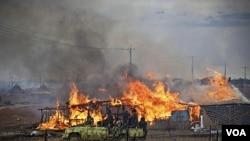 Kendaraan militer Sudan utara melewati kawasan bisnis di Abyei yang terbakar setelah pertempuran (28/5).