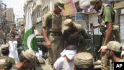 Pakistan army soldiers escort an alleged suspect arrested during a crackdown operation against militants in Bannu, Pakistan, July 16, 2012.