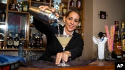 Cuban bartender Barbara Betancourt Bernal pours a daiquiri at a bar in Havana, Aug. 27, 2018.