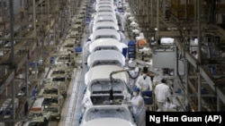 In this April 8, 2020, photo, employees work on a car assembly line at the Dongfeng Honda Automobile Co., Ltd factory in Wuhan in central China's Hubei province. (AP Photo/Ng Han Guan)