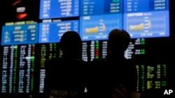 一對夫婦在日本東京交易所觀看股市看板。