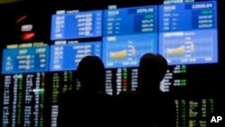 6月21日東京股票交易市場電子看版前﹐行人觀看股市下降的情形。