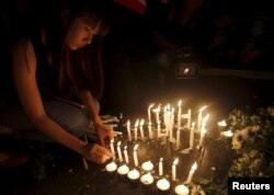 A woman lights candles at the Erawan shrine, the site of Monday's deadly blast, in central Bangkok, Thailand, August 18, 2015.